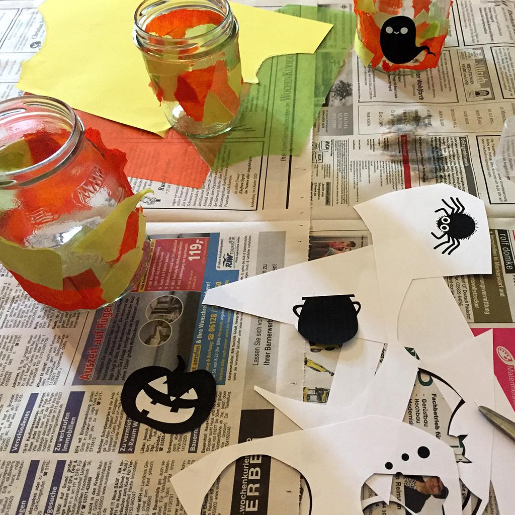 Halloween-Windlichter basteln: Figuren auf die Halloween-Windlichter kleben