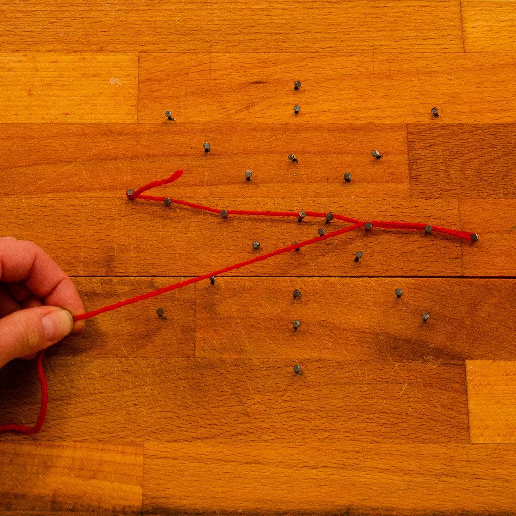 Spinnennetz basteln: Wollfaden um den Nagel wickeln